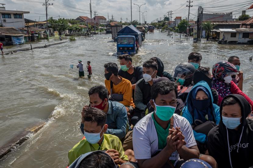 Sejumlah karyawan RS Sultan Agung menumpang truk evakuasi BPBD Semarang untuk dapat menembus banjir yang merendam jalur Pantura Jalan Raya Kaligawe - Genuk, Semarang, Jawa Tengah, Jumat (26/2/2021).
