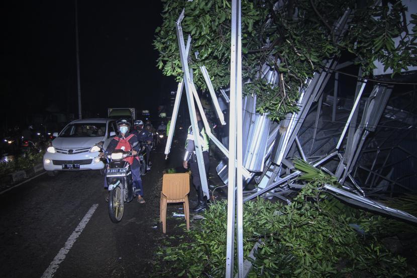 Sejumlah kendaraan melaju di samping atap ruko yang roboh di Jalan Kartini, Depok akibat angin kencang (ilustrasi)