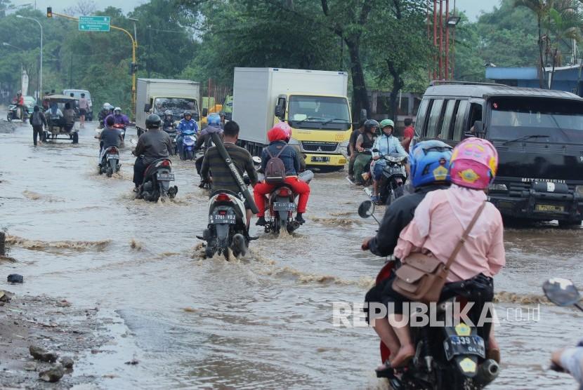Sejumlah kendaraan melintasi genangan air yang mulai membanjiri Jalan Anggadireja, Kecamatan Baleendah, Kabupaten Bandung, Kamis (8/11).