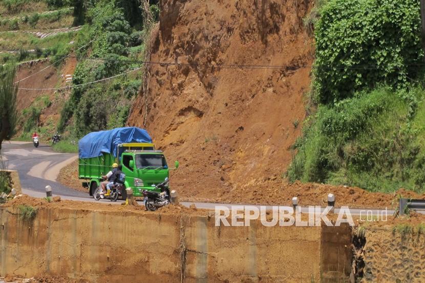 Sejumlah kendaraan melintasi lokasi tanah longsor.