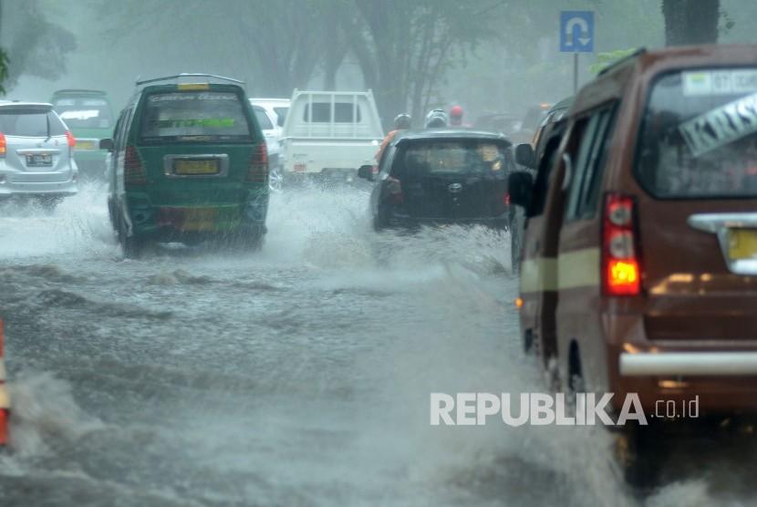 Sejumlah kendaraan menerobos banjir akibat luapan air drainase saat hujan deras yang mengguyur Kota Bandung, Kamis (22/11).