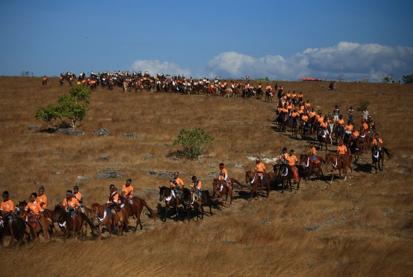 Sejumlah lelaki Sumba menunggangi kuda berbalut sarung tenun ikat Sumba dalam acara Parade Kuda dari Savana Walakiri menuju Pantai Walakiri pada Festival 1001 Kuda Sandelwood di Sumba Timur, NTT, Kamis (12/7).