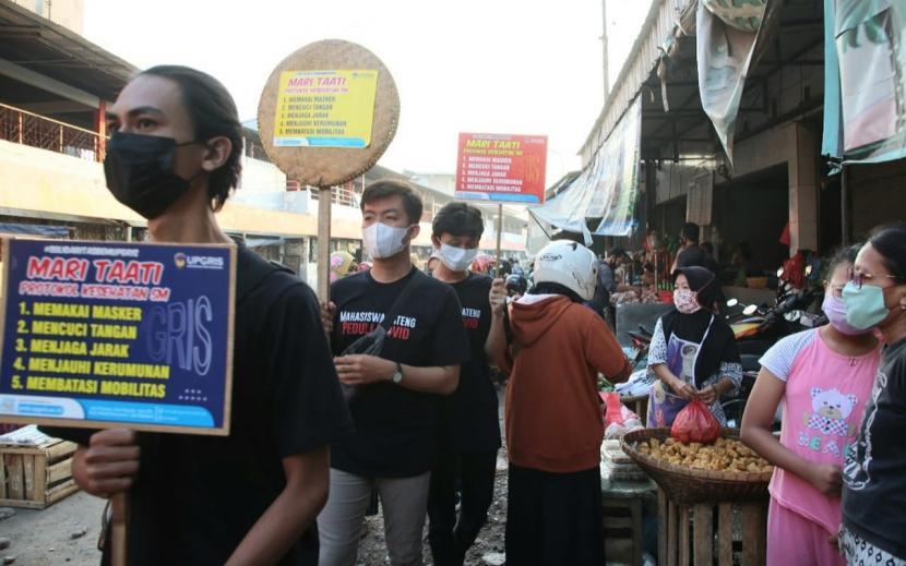 Sejumlah mahasiswa Universitas PGRI Semarang (Upgris) melakukan edukasi protokol kesehatan dan pembagian masker di tengah- tengah aktivitas warga pasar Pegerongan, Kota Semarang, Jumat (30/7). Aksi sosial ini dilakukan untuk mendorong disiplin penerapan protokol kesehatan di pasar tradisional tersebut.