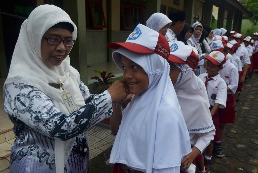 Sejumlah murid Sekolah Dasar(SD) berjajar antre untuk bersalaman kepada gurunya sambil mengucapkan Selamat Hari Guru di halaman Sekolah Dasar 1 Mlati Lor Kudus, Jawa Tengah, Jumat (25/11).