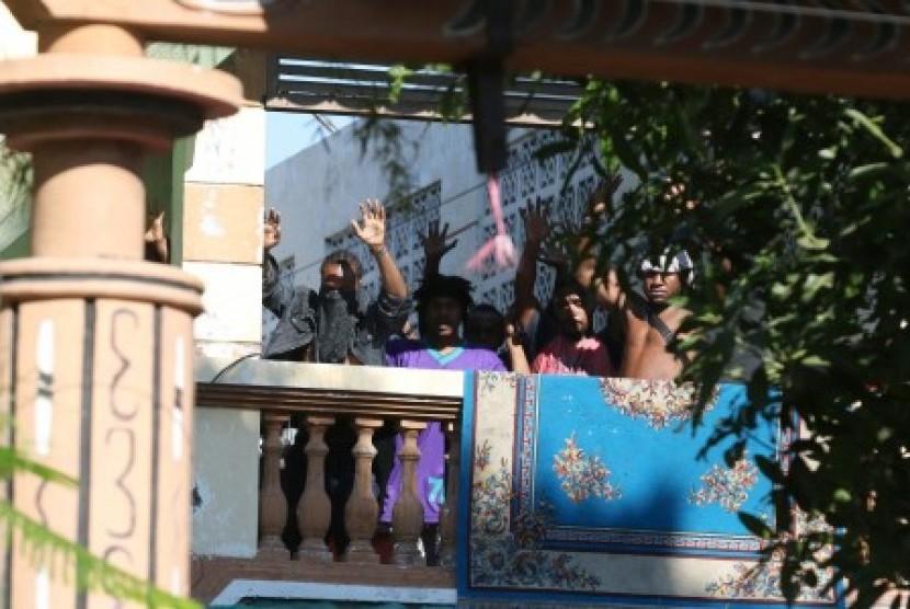 Sejumlah orang keluar dan mengangkat tangannya di Asrama Mahasiswa Papua di Jalan Kalasan 10, Surabaya, Jawa Timur, Sabtu (17/8/2019).