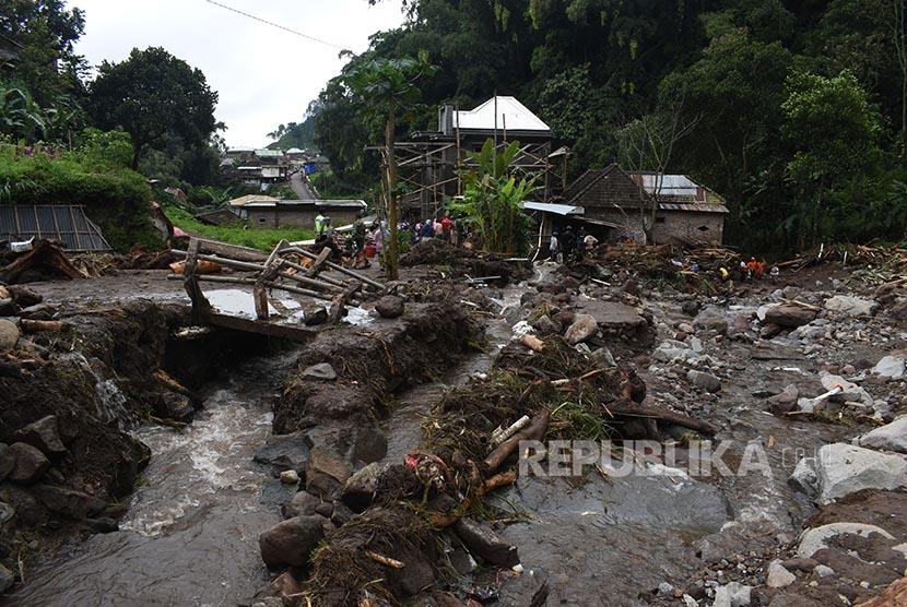 Sejumlah orang membersihkan material yang terbawa banjir bandang aliran lereng Gunung Lawu di Ngancar, Plaosan, Magetan, Jawa Timur, Senin (10/10).