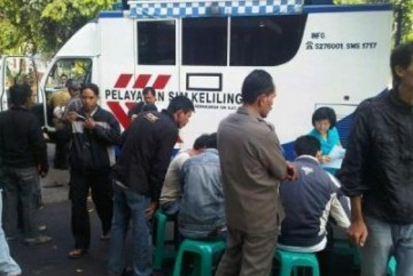 Sejumlah orang sedang sibuk mempersiapkan syarat-syarat untuk mengurus perpanjangan SIM dan STNK di mobil pelayanan keliling.