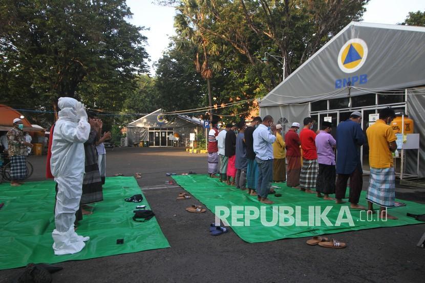 Sejumlah pasien COVID-19 dan tenaga kesehatan menunaikan shalat Idul Fitri di halaman Rumah Sakit Lapangan Indrapura (RSLI) di Surabaya, Jawa Timur, Kamis (13/5/2021). Pelaksanaan shalat Idul Fitri di RS Lapangan Indrapura tersebut diikuti sekitar 30 pasien dari Pekerja Migran Indonesia (PMI) dan puluhan tenaga kesehatan.