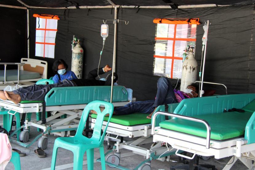 Sejumlah pasien menjalani perawatan di tenda darurat Rumah Sakit Umum Daerah (RSUD) Dumai, Riau, Selasa (27/7/2021). Tingkat keterisian tempat tidur (BOR) di rumah sakit tersebut sudah mencapai 100 persen karena ditempati oleh pasien COVID-19 sehingga pasien yang memiliki riwayat penyakit lain dirawat di tenda darurat agar tidak terinfeksi.