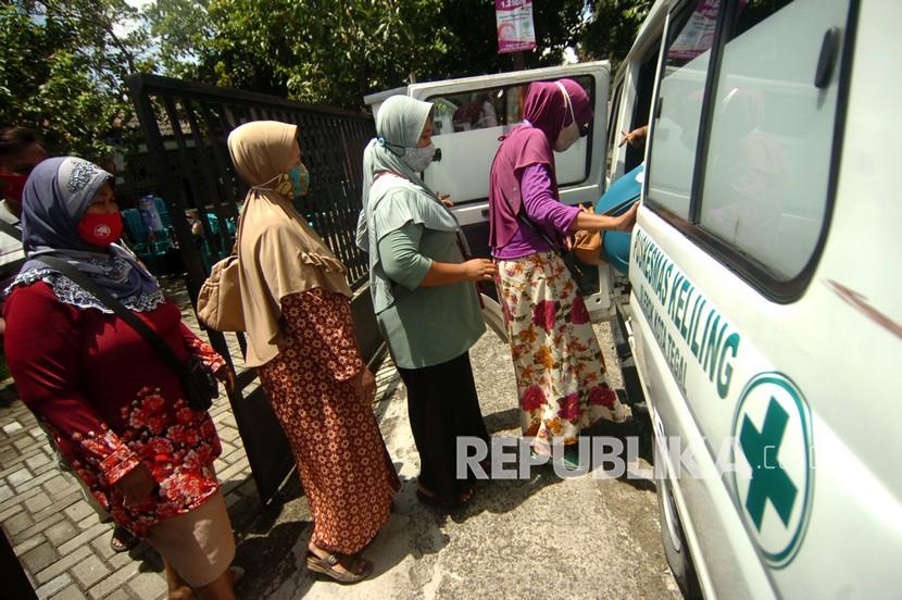 Sejumlah pedagang bersiap menaiki mobil usai vaksinasi Covid-19.
