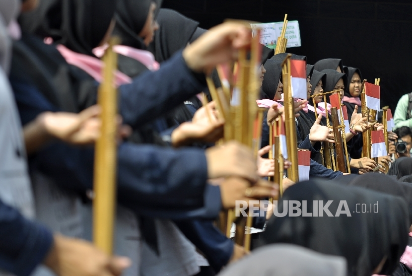Some students were playing traditional music instruments angklung.