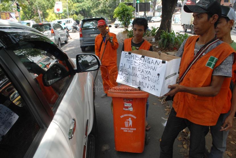 Sejumlah pekerja harian lepas (PHL) Dinas kebersihan DKI Jakarta meminta sumbangan kepada para pengendara yang melintas di kawasan Rawamangun, Jakarta Timur, Kamis (17/4). (Republika/Rakhmawaty La'lang)
