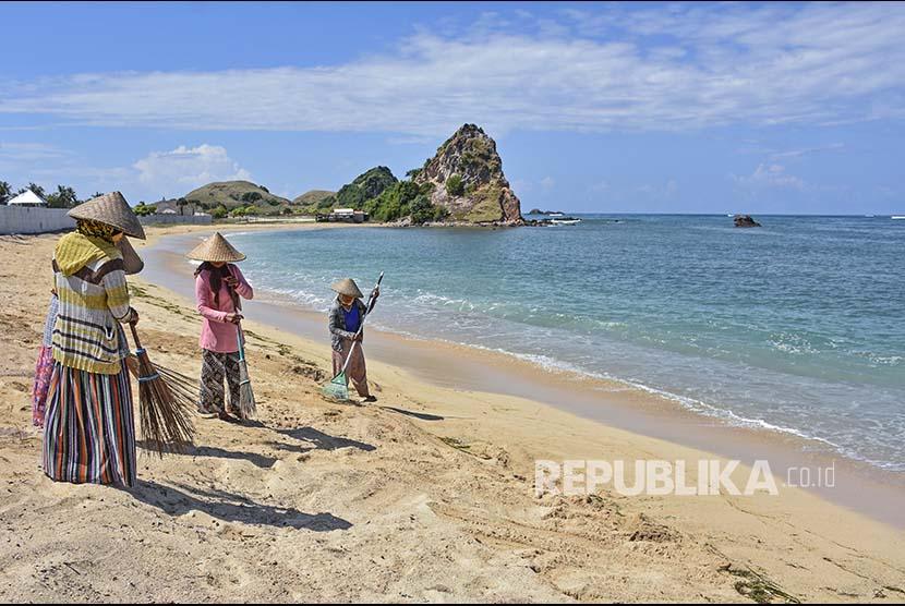 Sejumlah pekerja membersihkan pantai dekat area pembangunan Paramount Hotel & Residences di Kawasan Mandalika yang dikelola dan dikembangkan oleh BUMN Indonesia Tourism Development Corporation (ITDC) di Mandalika, Desa Kuta, Kecamatan Pujut, Praya, Lombok Tengah, NTB, Rabu (18/4).