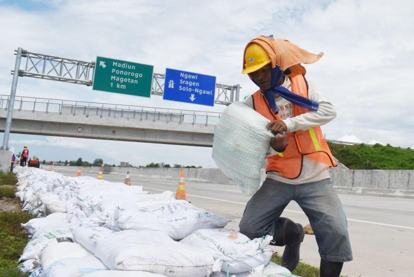 Sejumlah pekerja membuat tanggul dengan karung berisi pasir di tepi jalan tol Trans Jawa ruas Ngawi-Kertosono pada kilometer 603-604 yang sebelumnya terendam banjir di Desa Glonggong, Balerejo, Kabupaten Madiun, Jawa Timur, Sabtu (16/3/2019).