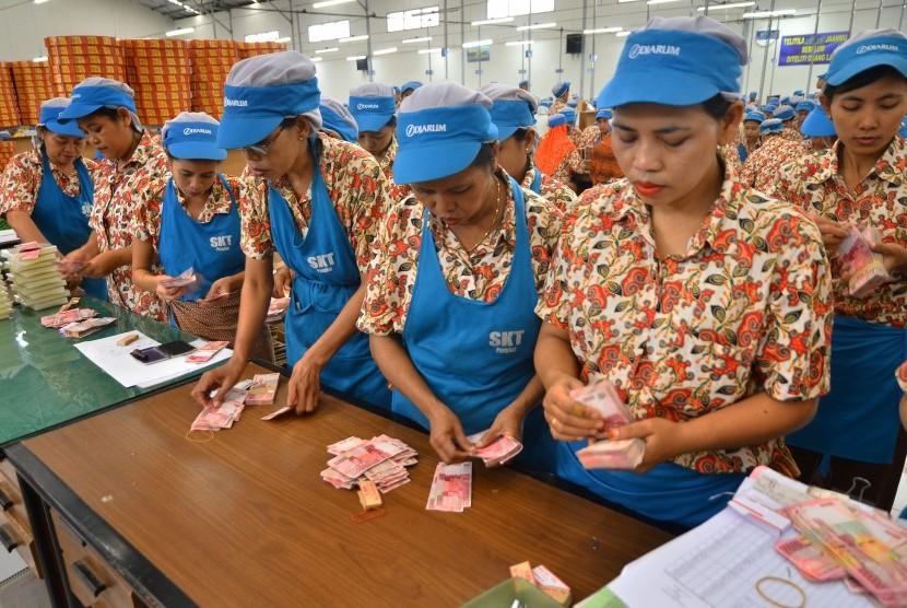 Sejumlah pekerja menghitung uang saat pembagian Tunjangan Hari Raya (THR) Lebaran di pabrik rokok PT. Djarum, Kudus, Jawa Tengah, Selasa (28/6).