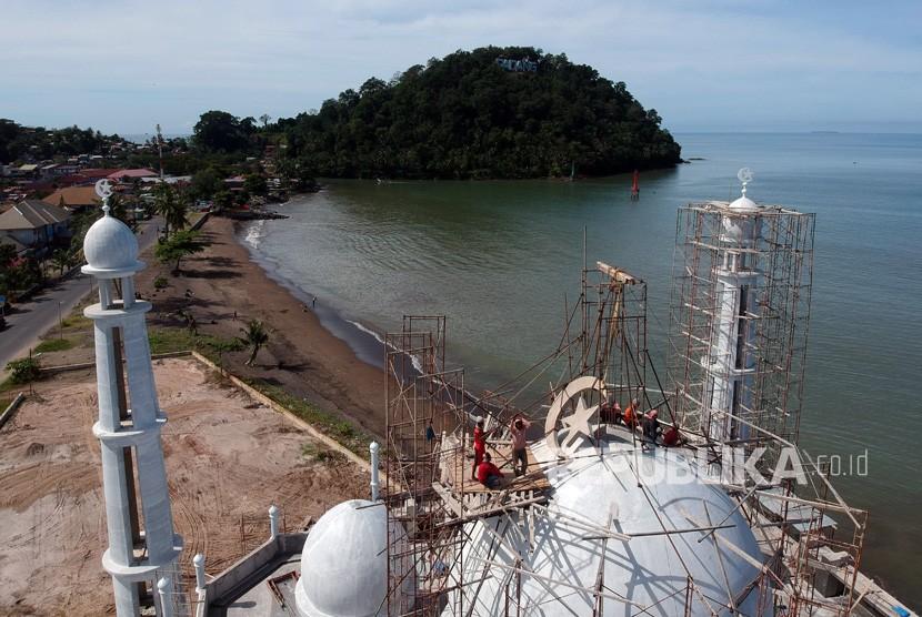 Sejumlah pekerja menyelesaikan pembangunan kubah masjid, di Pantai Padang, Sumatera Barat, Ahad (9/12/2018).