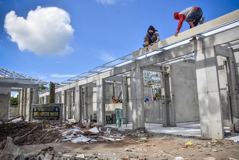 Sejumlah pekerja menyelesaikan pembangunan sekolah yang rusak akibat gempa di SDN 1 Guntur Macan, Lombok Barat, NTB, Kamis (7/2/2019).