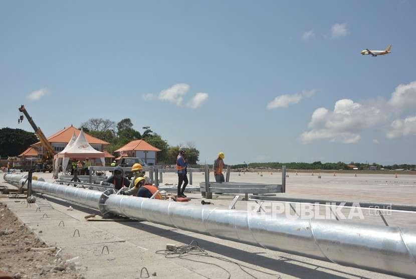 Sejumlah pekerja menyelesaikan proyek perluasan apron Bandara Internasional I Gusti Ngurah Rai, Bali, Selasa (18/9).