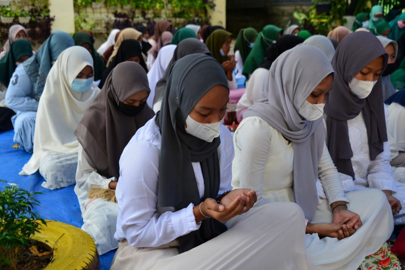 Sejumlah pelajar bersama guru mereka berdoa dan berzikir.