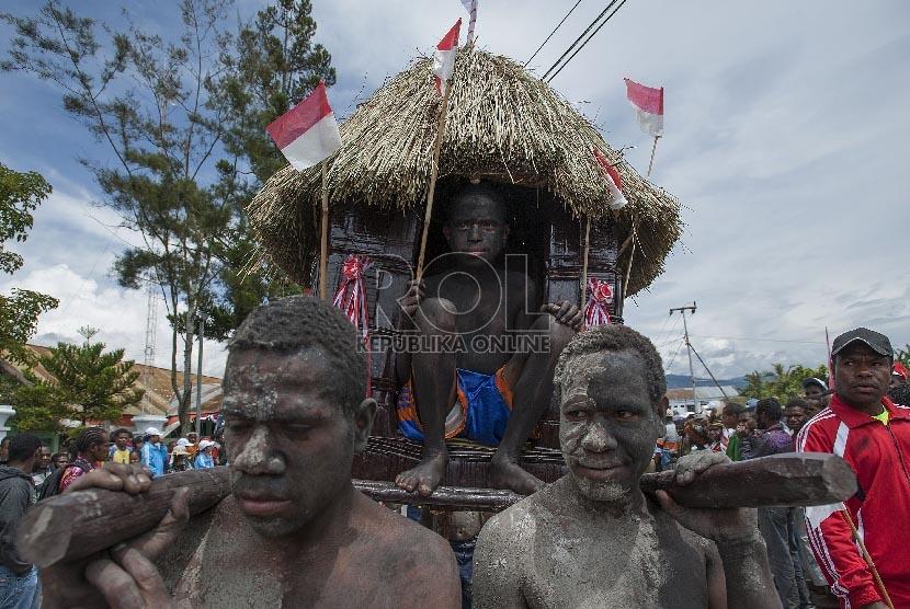 Sejumlah pelajar mengangkat replika Honai (rumah adat Papua) ketika mengikuti acara karnaval keliling kota di kota Wamena, Jayawijaya, Papua.