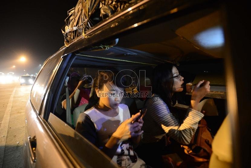 Sejumlah pemudik tujuan Pemalang menikmati makan sahur di bahu jalan tol Palimanan-Kanci (Palikanci), Cirebon, Jawa Barat, Selasa (14/7) dini hari.   (Republika/Raisan Al Farisi)