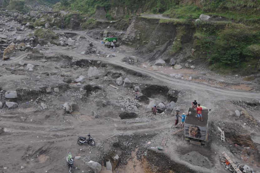 Sejumlah penambang memindahkan pasir secara manual ke truk pengangkut di Kali Woro, Kemalang, Klaten, Jawa Tengah, Jumat (25/6/2021). Pascaterjadinya awan panas guguran Gunung Merapi ke arah tenggara, aktivitas penambang pasir manual di Kali Woro tersebut masih berjalan dengan normal.