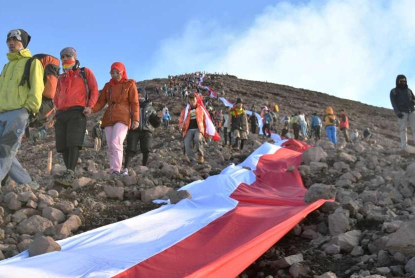 Sejumlah pendaki membentangkan bendera merah putih di lereng Gunung Kerinci, Jambi, Jumat (17/8).