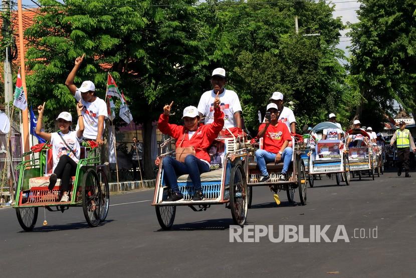 Sejumlah pendukung pasangan Capres dan Cawapres nomor urut 01 Joko Widodo - K.H. Ma'ruf Amin menuju tempat kampanye menggunakan becak di Banyuwangi, Jawa Timur, Senin (25/3/2019).
