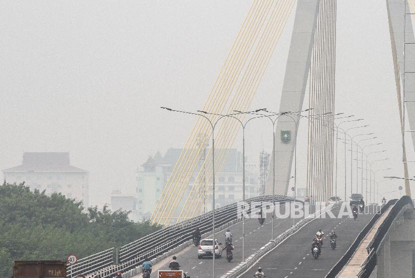 Sejumlah pengendara kendaraan bermotor melintas di atas jembatan Siak IV yang diselimuti kabut asap dampak kebakaran hutan dan lahan, di Pekanbaru, Riau, Selasa (6/8/2019). Kota Pekanbaru sudah sepekan diselimuti kabut asap dampak Karhutla, kondisi ini membuat Pemerintah Kota Pekanbaru menetapkan siaga darurat.