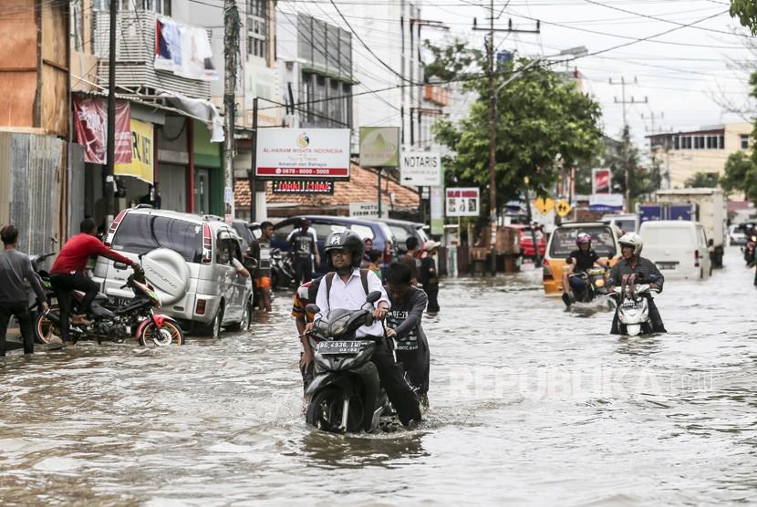 Sejumlah pengendara mendorong kendaraannya saat melintasi jalan yang terendam banjir dikawasan Sekip Bendung, Palembang, Sumatera Selatan, Selasa (13/11/2018).