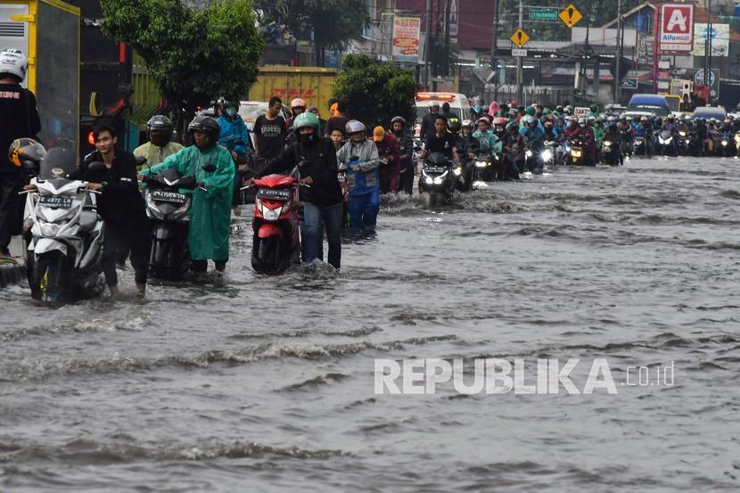 Sejumlah pengendara mendorong motor yang mogok saat melintasi Jalan Imam Bonjol yang tergenang air di Cikarang, Kabupaten Bekasi, Jawa Barat, Ahad(11/4/2021). Genangan air setinggi 30 cm akibat dari kualitas drainase yang buruk.