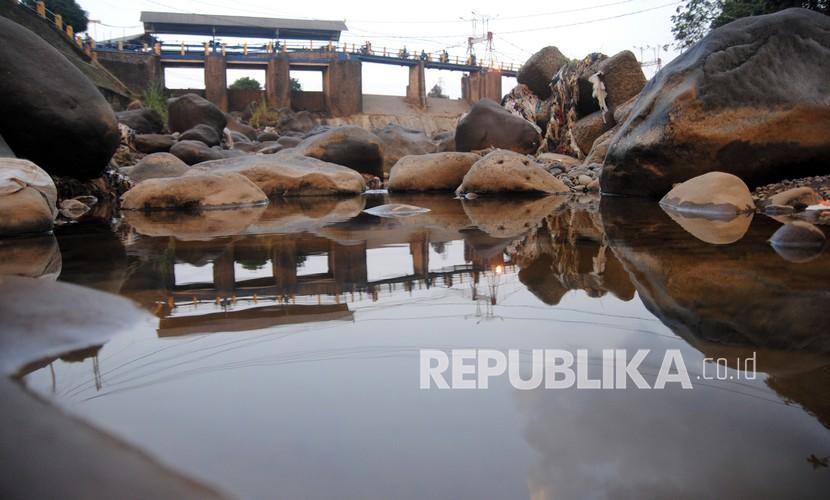 Sejumlah pengendara motor melintas di jembatan Bendung Katulampa, Kota Bogor, Jawa Barat, Rabu (28/7/2021). Memasuki musim kemarau, debit air di Bendung Katulampa, Bogor menyusut hingga 0 cm dari normal 40 ribu liter per detik menjadi 4000 liter per detik sehingga pasokan air untuk saluran irigasi pertanian ke wilayah Jakarta, Bogor dan Depok kapasitasnya berkurang.