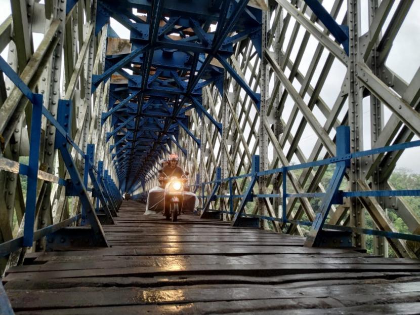 Sejumlah pengendara motor melintas Jembatan Cirahong, yang menghubungkan Kabupaten Ciamis dengan Kabupaten Tasikmalaya, Ahad (1/8). Sebelumnya jembatan itu sempat ditutup untuk lalu lintas kendaraan bermotor.