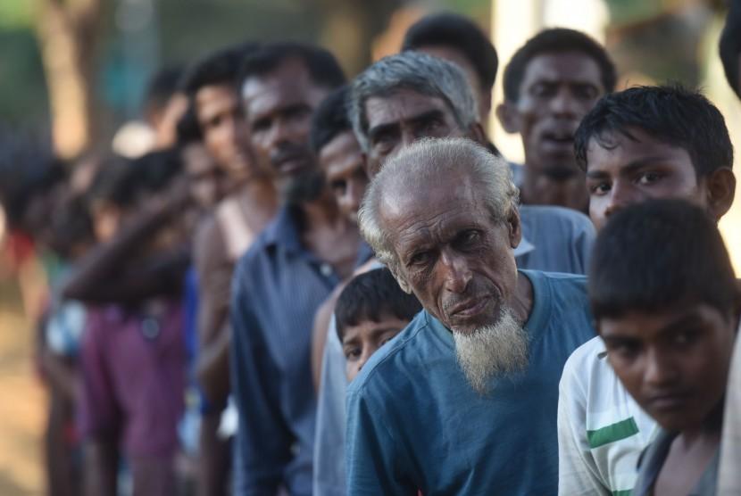 Sejumlah pengungsi Rohingya antri untuk mendapatkan paket makanan dari relawan Indonesia di Kamp Pengungsian Kutupalong, Cox Bazar, Bangladesh, Minggu (1/10).