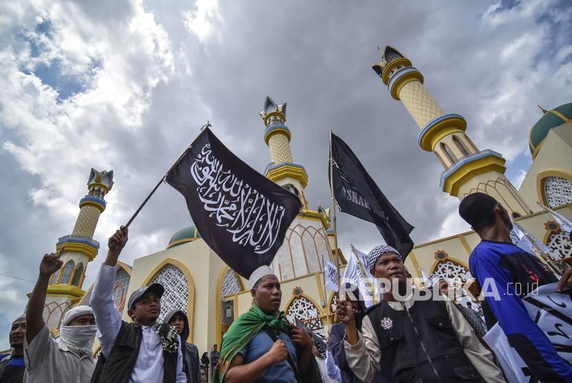 Sejumlah pengunjukrasa membawa bendera bertuliskan kalimat tauhid saat mengikuti aksi bela tauhid di Mataram, NTB, Jumat (26/10/18).