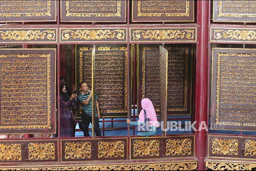 Sejumlah pengunjung berfoto di Alquran raksasa di Gandus, Palembang, Sumatera Selatan, Sabtu (3/6). Keberadaan Alquran raksasa (Alquran AL-Akbar) yang diukir di atas kayu trembesi itu menjadi destinasi wisata religi di Palembang.