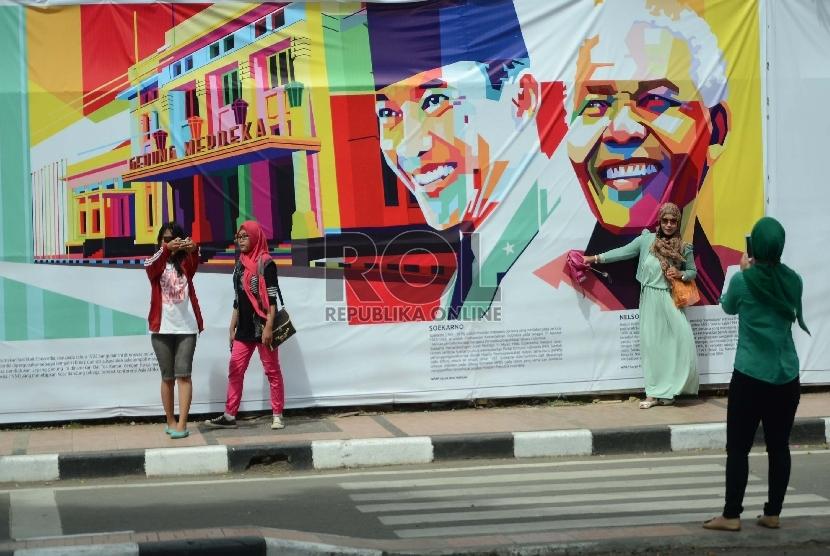 Sejumlah pengunjung berselfie ria di gambar Soekarno dan Nelson Mandela. Meski puncak perayaan Konferensi Asia Afrika (KAA) ke-60 telah usai namun kepadatan pengunjung masih terjadi di kawasan Gedung Merdeka, Jl Asia Afrika, Kota Bandung, Ahad (26/4).