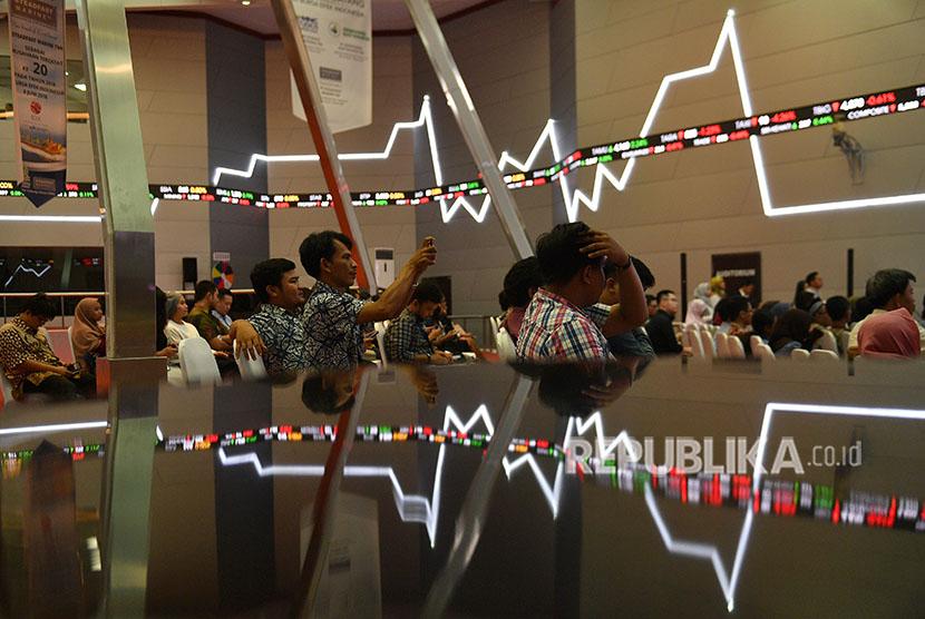 Sejumlah pengunjung duduk berlatar belakang pergerakan Indeks Harga Saham Gabungan (IHSG) di Bursa Efek Indonesia, Jakarta, Jumat (22/6).