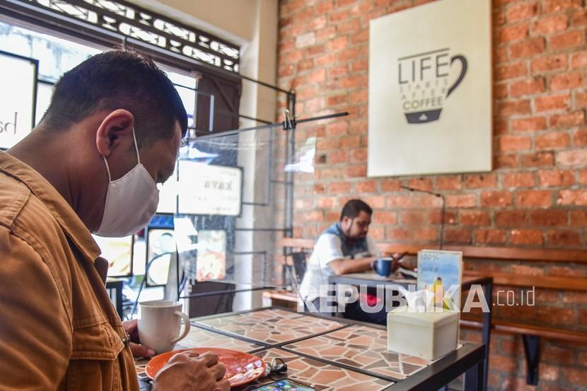 Sejumlah pengunjung kedai kopi duduk berjauhan dan dibatasi tirai plastik saat hari pertama PPKM (ilustrasi)