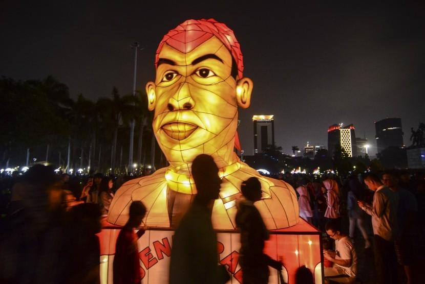 Sejumlah pengunjung melintas di dekat lampion karakter pahlawan nasional Jenderal Besar Sudirman pada acara Festival of Light di Monas, Jakarta Pusat, Sabtu (17/8). Festival lampion dan laser bertemakan HUT ke-74 Kemerdekaan RI itu berlangsung dari 14-25 Agustus 2019.