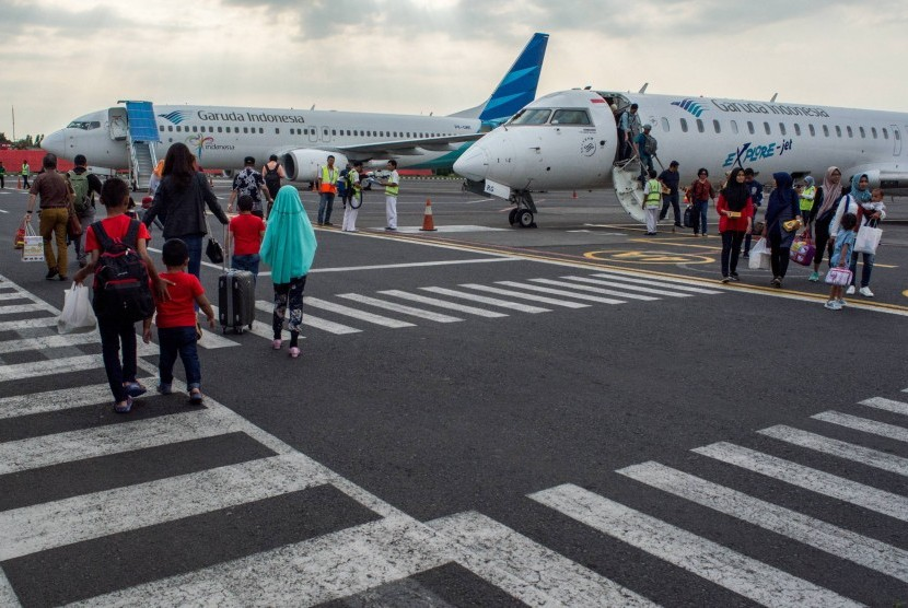 Sejumlah penumpang berjalan di area parkir pesawat saat tiba di Bandara Ahmad Yani, Semarang, Jawa Tengah, Ahad (18/6). PT Angkasa Pura I Bandar Udara Ahmad Yani memprediksi puncak arus mudik Lebaran 2017 akan terjadi pada H-2 Lebaran.