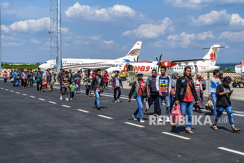 Sejumlah penumpang berjalan di area parkir pesawat saat tiba di Bandara Internasional Ahmad Yani, Semarang, Jawa Tengah, Senin (11/6).