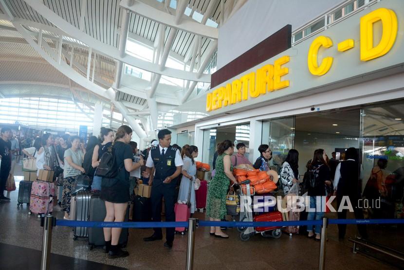 Sejumlah penumpang menunggu jadwal penerbangan di Bandara Ngurah Rai, Bali, Jumat (29/6).