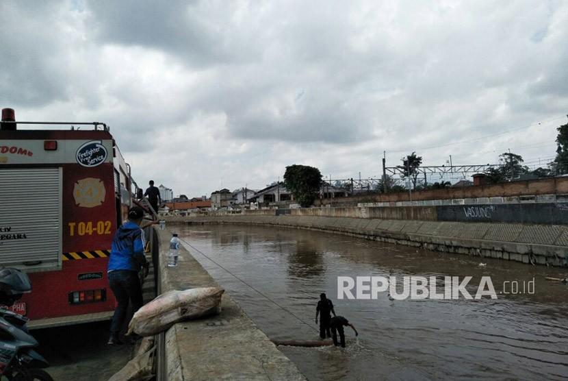 Sejumlah personel dari Suku Dinas Sumber Daya Air Jakarta Timur membersihkan sisa lumpur akibat luapan Sungai Ciliwung, kawasan Kampung Melayu.