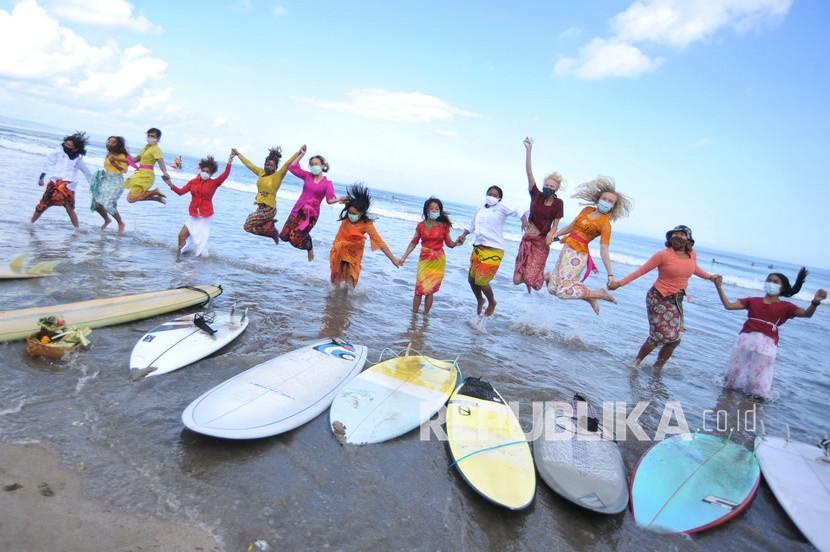 Sejumlah peselancar wanita yang mengenakan busana kebaya berfoto sebelum berselancar di Pantai Kuta, Badung, Bali, Jumat (16/4/2021). Kegiatan yang diikuti puluhan perempuan termasuk sejumlah WNA tersebut dilakukan untuk menyambut peringatan Hari Kartini serta membangkitkan sektor pariwisata Bali yang terdampak pandemi COVID-19.