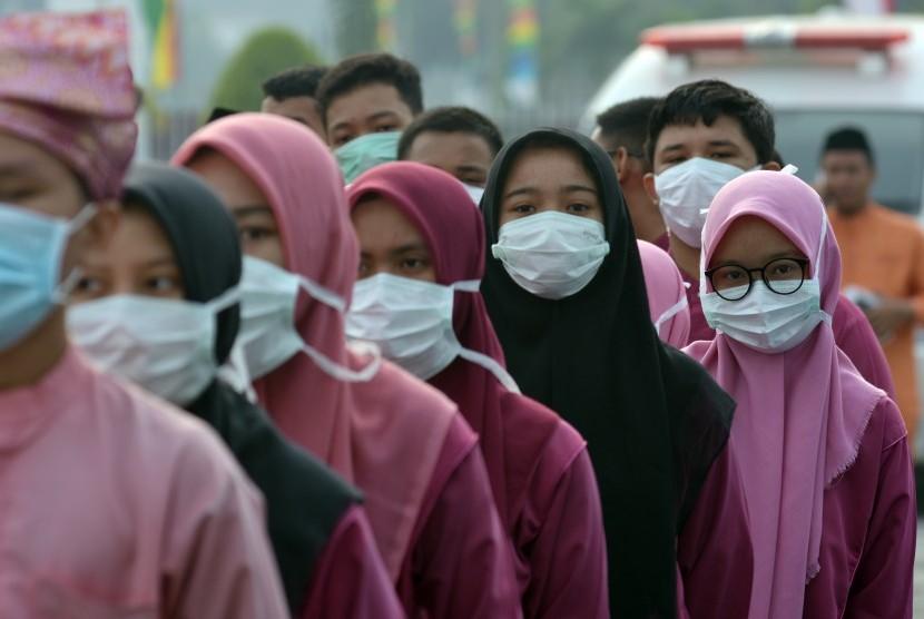 Sejumlah peserta upacara peringatan HUT ke-62 Provinsi Riau mengenakan masker medis akibat asap menyelimuti Kota Pekanbaru, Jumat (9/8/2019).