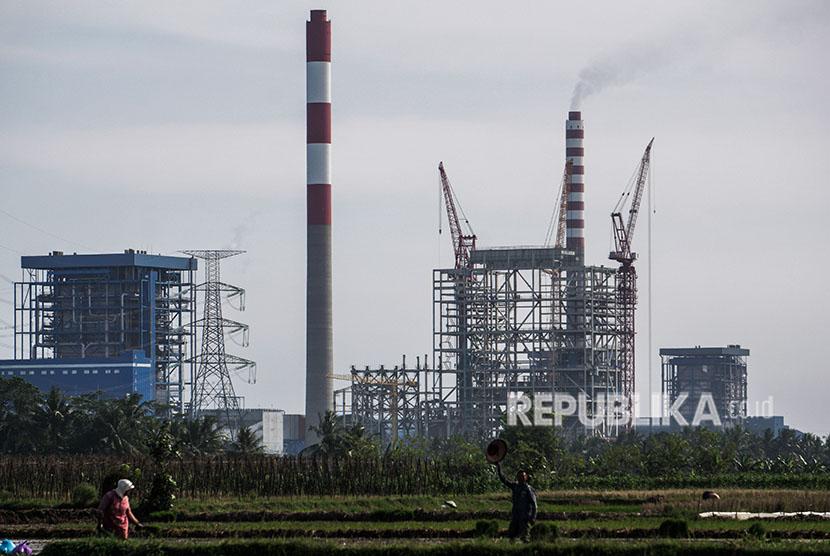 Sejumlah petani menggarap lahan sawahnya dengan latar belakang proyek pembangkit listrik tenaga uap (PLTU) Cilacap Ekspansi Fase 2, 1x1.000 Megawatt di Desa Karangkandri, Kesugihan, Cilacap, Jawa Tengah, Selasa (24/4).