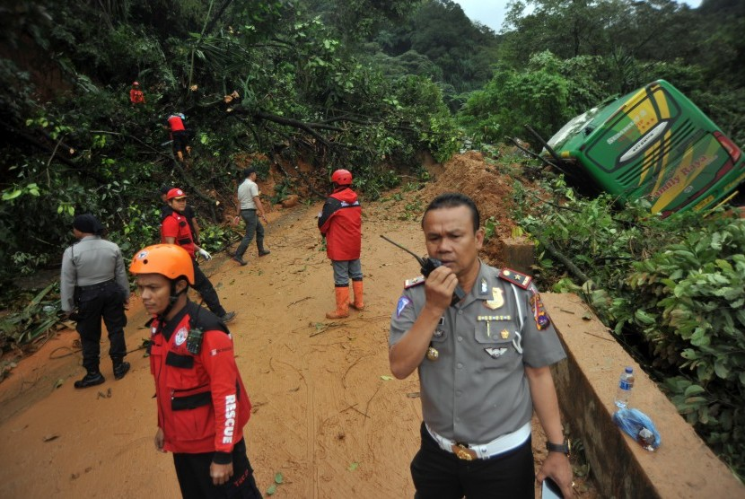 Sejumlah petugas berada di lokasi longsor yang menghantam tiga unit kendaraan, di Jalur Lintas Padang - Jambi, Panorama II Sitinjau Lauik, Padang, Sumatera Barat, Jumat (14/12/2018).