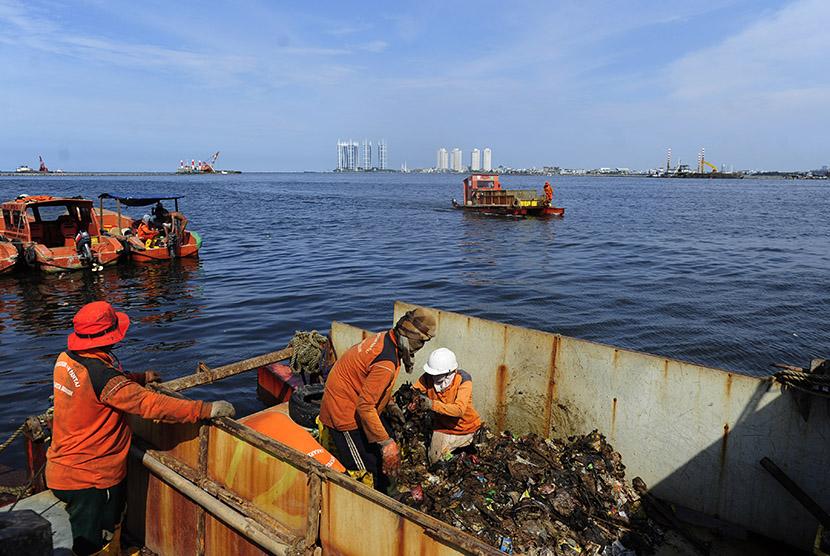 Sejumlah petugas kebersihan memindahkan sampah dari kapal ke truk pengangkut sampah