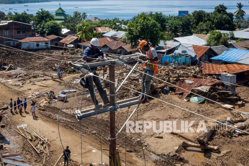 Sejumlah petugas memperbaiki jaringan listrik yang terputus akibat banjir bandang di Adonara Timur, Kabupaten Flores Timur, Nusa Tenggara Timur (NTT), Kamis (8/4/2021). Pemulihan infrastruktur dilakukan untuk kembali menghidupkan perekonomian masyarakat setempat pascabencana alam yang terjadi pada Minggu (4/4) tersebut.
